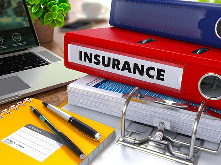 Red Ring Binder with Inscription Insurance on Background of Working Table with Office Supplies, Laptop, Reports. Toned Illustration. Business Concept on Blurred Background.-1