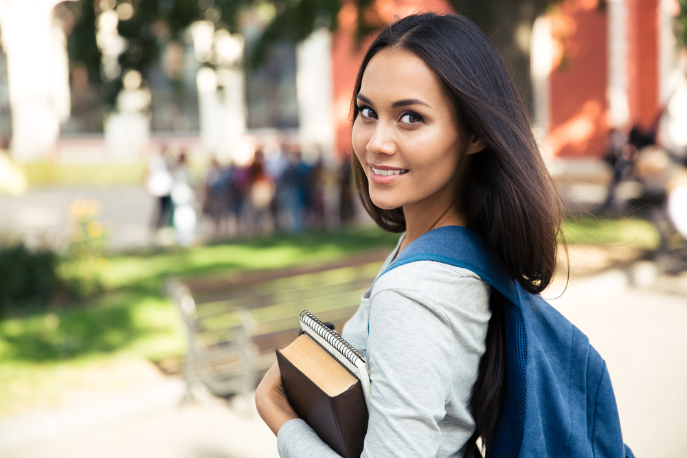Portrait of a happy female student looking back at camera outdoors