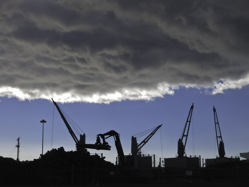 Storm cloud over silhouettes of cranes lifting logs to be shipped from seaport of Astoria, Oregon
